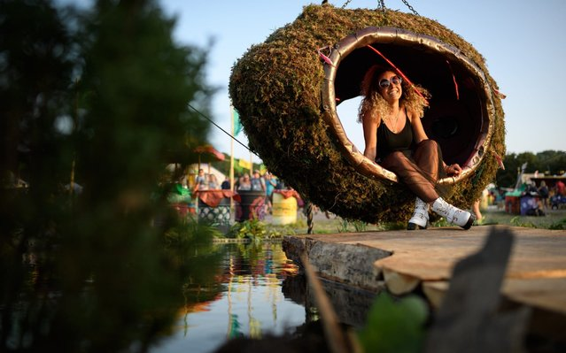 A festival-goer poses for a photograph within a hanging chair on day two of Glastonbury Festival at Worthy Farm, Pilton on June 27, 2019 in Glastonbury, England. Glastonbury is the largest greenfield festival in the world, and is attended by around 175,000 people. (Photo by Leon Neal/Getty Images)