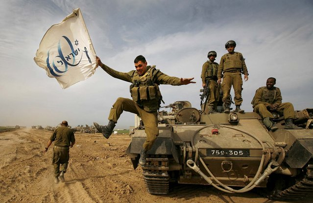 An Israeli soldier jumps off an armored vehicle carrying a flag of Israel's 60th anniversary as he celebrates with his unit their return from the Gaza Strip on the Israeli side of the border, Jan. 16, 2009. (Photo by Anja Niedringhaus/AP Photo)