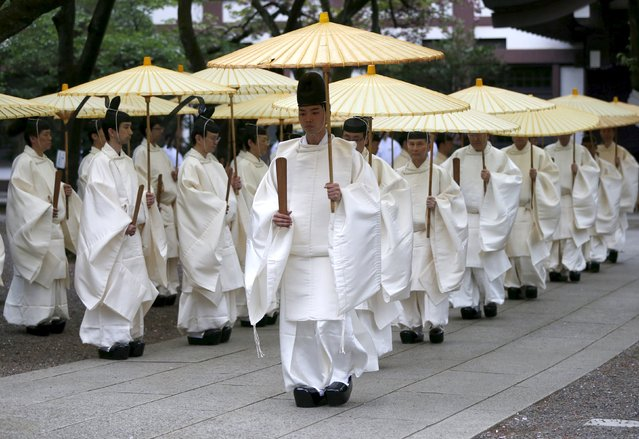 Shinto priests holding traditional umbrellas walk to the main shrine for a ritual to cleanse themselves during the annual Spring Festival at the Yasukuni Shrine in Tokyo, Japan, April 21, 2016. (Photo by Issei Kato/Reuters)