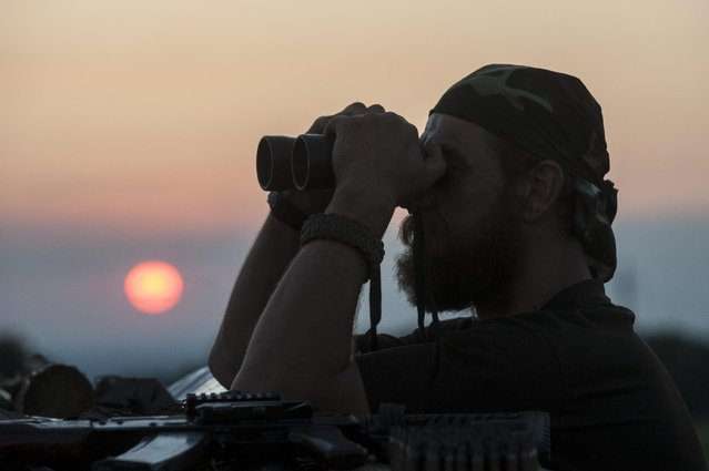 In this photo taken Monday, June 22, 2015, a Ukrainian serviceman from the Kiev-2 volunteer battalion uses binoculars at the frontline in the village of Krymske, east Ukraine. (Photo by Evgeniy Maloletka/AP Photo)