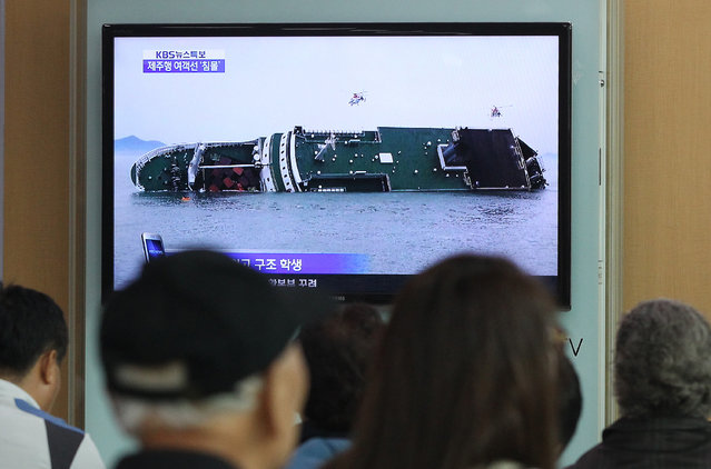 People watch a TV news program showing a sinking passenger ship, at Seoul Railway Station in Seoul, South Korea, Wednesday, April 16, 2014. The South Korean passenger ship carrying more than 470 people, including many high school students, is sinking off the country's southern coast Wednesday after sending a distress call, officials said. There are no immediate reports of causalities. (Photo by Ahn Young-joon/AFP Photo)