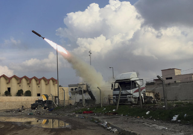 Iraqi security forces fire a rocket towards Islamic State Group positions in Mosul, Iraq, Monday, March 20, 2017.   Iraqi forces are coming closer to recapturing the city of Mosul from the militant group. (Photo by Mohammed Numan/AP Photo)