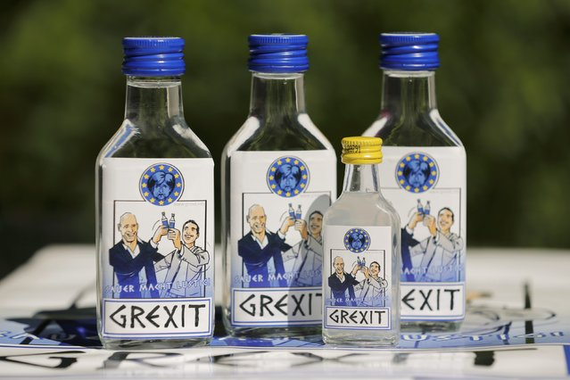 """Samples of a vodka schnapps and a sour vodka called """"Grexit"""" labelled with the caricatures of Greek Prime Minister Alexis Tsipras (R) and Finance Minister Yannis Varoufakis happily raising their glasses under a miserable-looking German Chancellor Angela Merkel, are displayed at the home of German entrepreneur Uwe Dahlhoff in Hamm, western Germany, June 30, 2015. (Photo by Wolfgang Rattay/Reuters)"""