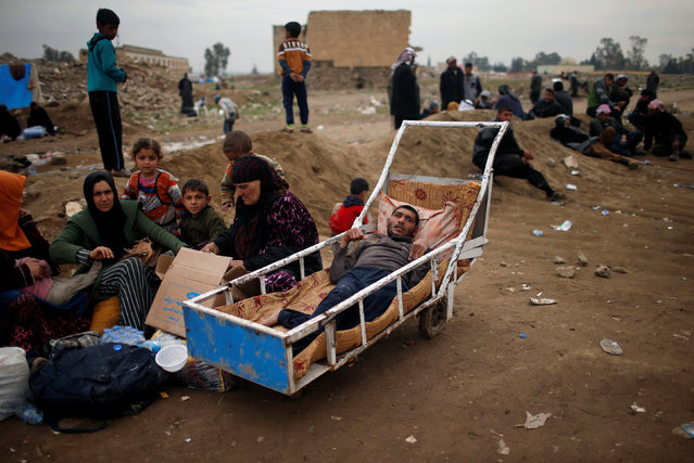 Displaced Iraqis who had fled their homes wait to enter Hammam al-Alil camp south of Mosul, Iraq March 21, 2017. (Photo by Suhaib Salem/Reuters)