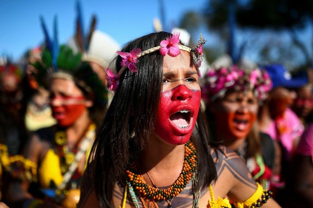 """Brazilian indigenous women march towards the Ministry of Health office during a protest against budget cuts, in Brasilia on August 12, 2019. Indigenous women marched on Tuesday in Brasilia to claim their rights and to denounce the """"dismantling"""" of the environmental and human rights policy by the government of Brazil's President Jair Bolsonaro. (Photo by Sergio Lima/AFP Photo)"""