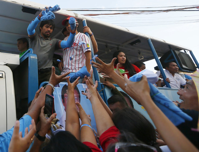 Filipino boxer and Congressman Manny Pacquiao, who is running for senator in Monday's national elections, throws souvenir t-shirts, candies and wrist bands to supporters during his campaign sortie with Presidential candidate Vice-president Jejomar Binay in Navotas north of Manila, Philippines Friday, May 6, 2016. (Photo by Bullit Marquez/AP Photo)