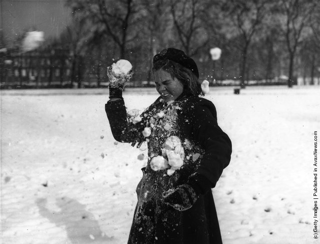 1954: A young girl being hit by a snowball whilst playing in St James Park, London, after a night of heavy snowfall