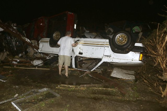 John Ward, an automobile and RV dealer, looks at tornado damage to one of his trucks in Mayflower, Ark., Sunday, April 27, 2014. At least 16 people died Sunday night in Arkansas as a tornado carved an 80-mile path of destruction. (Photo by Danny Johnston/AP Photo)