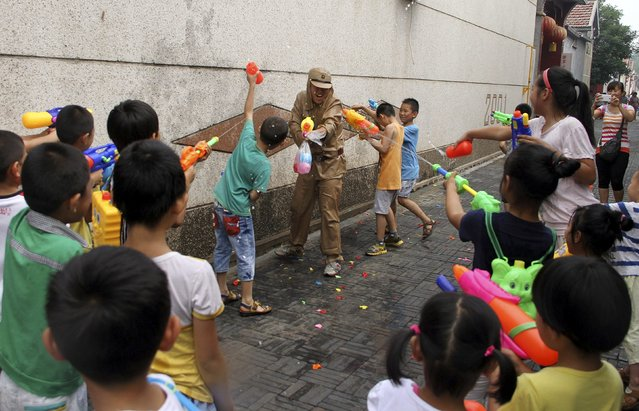A staff of a tourism resort dressed as Japanese soldiers squirts water guns as he takes part in a mock fight with children visitors during an event to mark the 70th anniversary of the end of the Sino-Japan War, in Binzhou, Shandong province, China, July 5, 2015. (Photo by Reuters/Stringer)