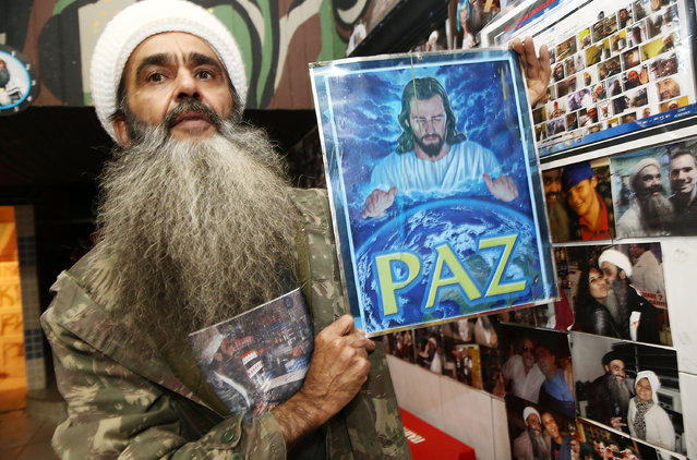 """Osama bin Laden lookalike Ceara Francisco Helder Braga Fernandes poses with a portrait of Jesus in his """"Bar do Bin Laden"""" on April 29, 2014 in Sao Paulo, Brazil. Braga says he was known as the """"Beard Man"""" before 9/11 but became known as a Bin Laden lookalike following the 9/11 attacks. He says he is Christian and continues to play the role to support his business. (Photo by Mario Tama/Getty Images)"""