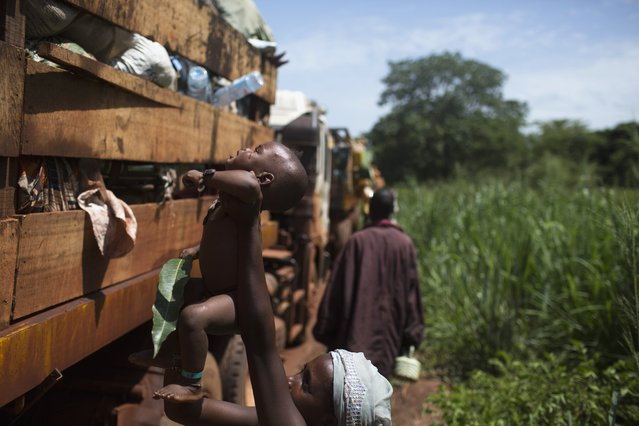 A woman passes her child on the top of a truck during a break from her journey towards Chad's border escorted by African Union operation in CAR (MISCA) a few kilometres after the northern town of Kaga Bandoro April 29, 2014. Of the remaining Muslims that have been sheltered from sectarian violence in the neighbourhood of PK12 in Bangui, over one thousand have been evacuated towards the northern town of Kabo and Sido on the border with Chad. (Photo by Siegfried Modola/Reuters)
