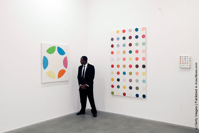 A security guard looks at part of the artist Damien Hirst's exhibition The Complete Spot Paintings