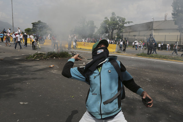 A demonstrator throws stones during anti-government protests in Caracas, Venezuela, Wednesday, April 19, 2017. (Photo by Fernando Llano/AP Photo)