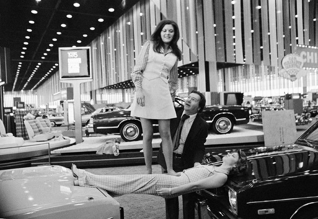 Carol Richardson, 21, of Southgate, who has been hypnotized, supports Cheri Trudell, 19, of Rochester, as she lies with her head and feet resting on hoods of two Dodge autos at Chicago's McCormick Place, February 21, 1975 on the eve of the opening of the annual automobile show. Hypnotist Karrell Fox of Farmington helps Cheri keep her balance. All are from Michigan. (Photo by Larry Stoddard/AP Photo)