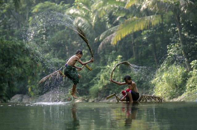 """Water War"". This game the children uses the kray leaves in his belt as a weapon. Photo location: Rumpin, Bogor, West Java. (Photo and caption by Saiful Shyrazy/National Geographic Photo Contest)"