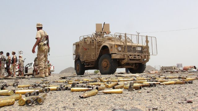 A Southern Resistance fighter walks past an armoured personnel carrier taken by resistance fighters from Houthi fighters in the Emran outskirts of Yemen's southern port city of Aden July 13, 2015. The Houthis, who took over the capital Sanaa last September, have been battling local fighters in the south for three months. (Photo by Reuters/Stringer)