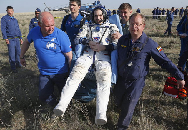 Russian space agency rescue crew members carry U.S. astronaut Rick Mastracchio shortly after the landing of the Russian Soyuz TMA-11 space capsule,  south-east of the town Dzhezkazgan,  Kazakhstan, May 14, 2014. A Soyuz space capsule with Japanese astronaut Koichi Wakata, Russian cosmonaut Mikhail Tyurin and U.S. astronaut Rick Mastracchio, returning from a five-month mission to the International Space Station, landed safely Wednesday on the steppes of Kazakhstan. (Photo by Dmitry Lovetsky/Reuters)