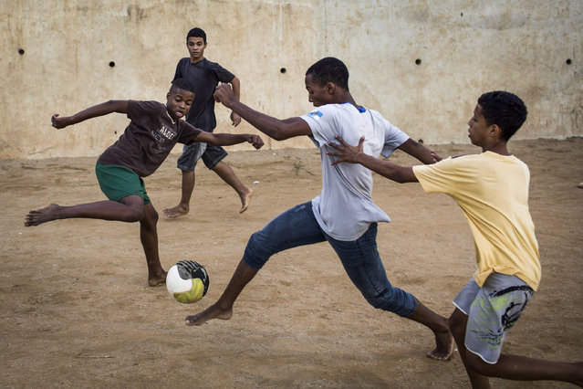 Young residents play soccer at the Sao Carlos slum in Rio de Janeiro, Brazil, Monday, May 12, 2014. As opening day for the World Cup approaches, people continue to stage protests, some about the billions of dollars spent on the World Cup at a time of social hardship, but soccer is still a unifying force. The international soccer tournament will be the first in the South American nation since 1950. (Photo by Felipe Dana/AP Photo)