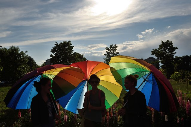 People hold raibow umbrellas to celebrate International Day Against Homophobia in the front of the Romanian Parliament building in Bucharest May 17, 2016. The International Day Against Homophobia, Transphobia and Biphobia (IDAHO) is observed on May 17 and aims to coordinate international events that raise awareness of LGBT rights violations and stimulate interest in LGBT rights work worldwide. (Photo by Daniel Mihailescu/AFP Photo)