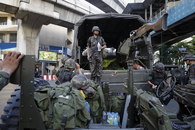 Thai soldiers take their positions in the middle of a main intersection in Bangkok's shopping district, on May 20, 2014. (Photo by Damir Sagolj/Reuters)