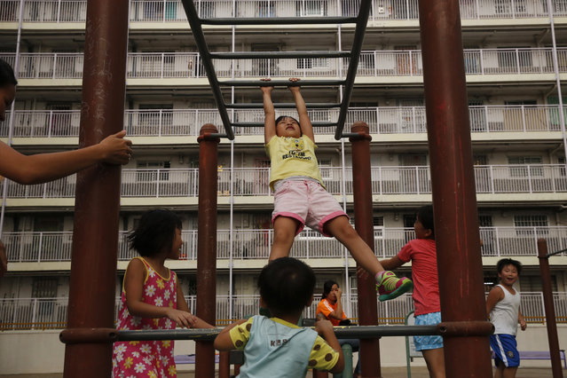 In this Tuesday, July 7, 2015 photo, children play at a park in a public housing complex in Hong Kong. (Photo by Kin Cheung/AP Photo)