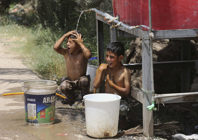 Iraqi displaced children cool themselves with water at a camp for internally displaced people in Baghdad's southern district of Dora on Tuesday, July 7, 2015. (Photo by Karim Kadim/AP Photo)