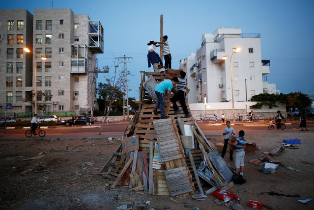 Ultra-Orthodox Jewish boys stand on a pile of wood to be burnt later as part of celebrations for the Jewish holiday of Lag Ba'Omer in the city of Ashdod, Israel May 25, 2016. This day marks the hillula (celebration, interpreted by some as anniversary of death) of Rabbi Shimon bar Yochai, a Mishnaic sage and leading disciple of Rabbi Akiva in the 2nd century, and the day on which he revealed the deepest secrets of kabbalah in the form of the Zohar (Book of Splendor), a landmark text of Jewish mysticism. (Photo by Amir Cohen/Reuters)
