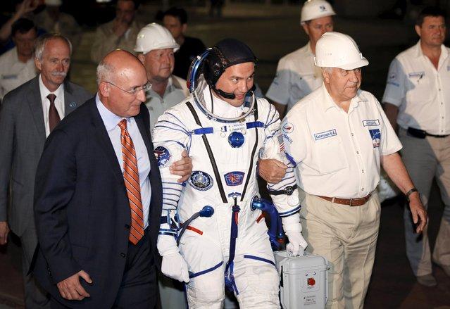 The International Space Station (ISS) crew member Kjell Lindgren of the U.S. (C) walks to board the Soyuz TMA-17M spacecraft at the Baikonur cosmodrome, Kazakhstan, July 23, 2015. (Photo by Yuri Kochetkov/Reuters)