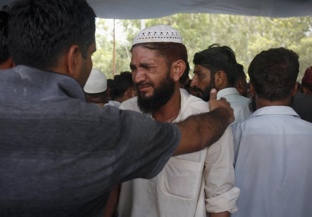 A relative of an Airport Security Force soldier killed at Jinnah International Airport is comforted by a man during funeral prayers at ASF Headquarters in Karachi, June 9, 2014. REUTERS/Athar Hussain