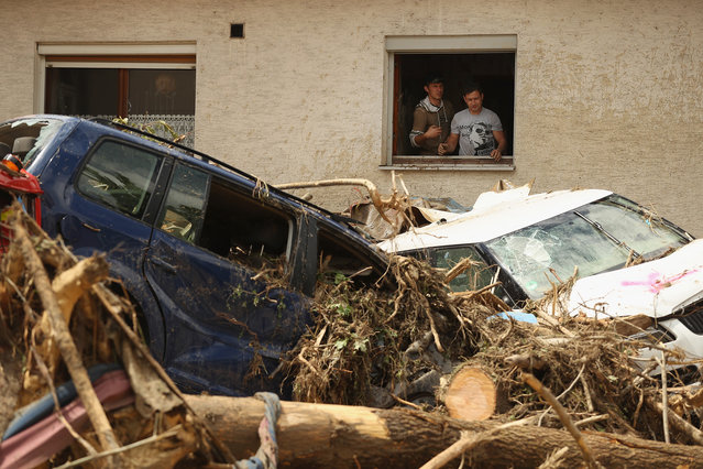 Two men throw ruined household items from the window of a house next to cars smashed among debris following a furious flash flood the night before on May 30, 2016 in Braunsbach, Germany. (Photo by Sean Gallup/Getty Images)