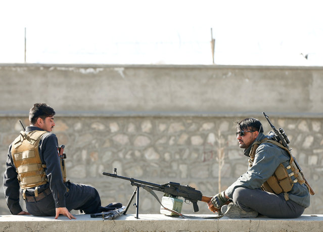 Afghan policemen sit near the site of a blast and gunfire between Taliban and Afghan forces in PD 6 as policemen keep watch in Kabul, Afghanistan March 1, 2017. (Photo by Omar Sobhani/Reuters)