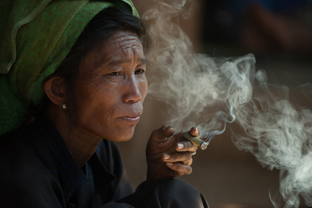"""Cheroot"". While walking through a five day market upriver from Inle Lake, Myanmar, I saw this Pa O tribal woman taking a thoughtful break with the ubiquitous hand rolled cheroot. Photo location: Inn Dein (Innthein), Shan State, Myanmar. (Photo and caption by Zoe Kritzler/National Geographic Photo Contest)"