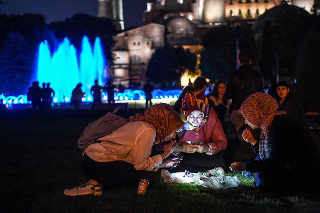 Women look at their cell phones after breaking fast on May 27, 2017 at the Blue Mosque Square in Istanbul, during the first day of the holy month of Ramadan. The world's nearly 1.5 billion Muslims on May 27 began Ramadan, the holy month of dawn-to-dusk fasting and prayers. It is sacred to Muslims because tradition says the Koran was revealed to the Prophet Mohammed during that month. (Photo by Ozan Kose/AFP Photo)