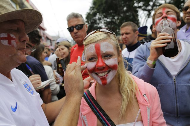 A soccer fan stands still as her face is painted the team colors of the British national soccer team, near Arena Corinthians stadium, before the start of the group D World Cup soccer match between Uruguay and England in Sao Paulo, Brazil, Thursday, June 19, 2014. (Photo by Nelson Antoine/AP Photo)