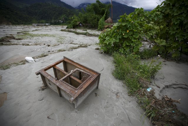 A kitchen cabinet, washed away by a flood due to heavy rainfall, lies on a riverbank in Kaski District July 31, 2015. Landslides triggered by torrential rain in Nepal swept through villages on Thursday, killing at least 30 people close to the nation's most popular trekking circuit, home ministry officials said. (Photo by Navesh Chitrakar/Reuters)