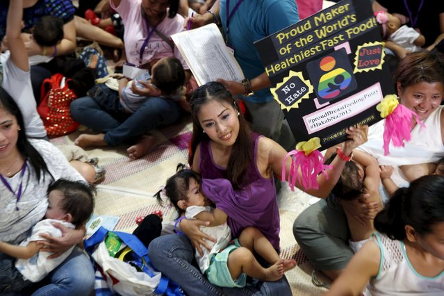 "A mother displays a placard as she breastfeeds her child in Mandaluyong city, Metro Manila in the Philippines August 1, 2015. A statement from a non-government organization Breastfeeding Pinays said that in celebration of the National Breastfeeding Awareness Month in August, they organized a one day breastfeeding activity called ""Hakab Na 2015"". (Photo by Erik De Castro/Reuters)"