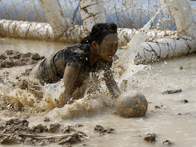A female goalkeeper chases a ball during a match at the swamp soccer China tournament in Beijing, June 26, 2014. The 32 teams from across the country participated in the soccer event to celebrate the 2014 World Cup in Brazil. (Photo by Kim Kyung-Hoon/Reuters)
