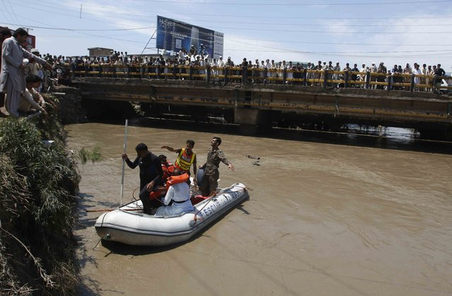 Rescue workers deploy a boat as local residents watch after heavy rainfall caused flooding in Peshawar, Pakistan, July 27, 2015. (Photo by Khuram Parvez/Reuters)