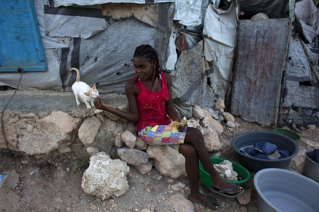 In this June 26, 2015 photo, a young woman shares a cracker with a kitten in a post-earthquake tent camp that residents are hoping to turn into a permanent neighborhood in Port-au-Prince, Haiti. More than five years after a magnitude 7.0 quake destroyed much of the capital, there are few visible signs of the disaster and the vast majority of the people who were displaced have found homes. (Photo by Rebecca Blackwell/AP Photo)