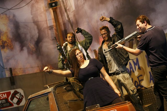 """Visitors pose with impersonators of the """"Homefront: The Revolution"""" video game characters, published by Deep Silver, during the Gamescom fair in Cologne, Germany August 5, 2015. The Gamescom convention, Europe's largest video games trade fair, runs from August 5 to August 9. (Photo by Kai Pfaffenbach/Reuters)"""