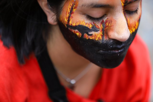A demonstrator who has symbolically painted a kangaroo running away from the fire on her face is taking part in a protest against climate policy in front of the Australian Embassy in Buenos Aires, Argentina on January 10, 2020. Among others, the organization Extinction Rebellion had called for protest. Since the big bushfires began, more than ten million hectares of land have been burned and at least 26 people have lost their lives. The plume of bush fires in Australia has reached Chile and Argentina. (Photo by Matias Baglietto/Reuters)
