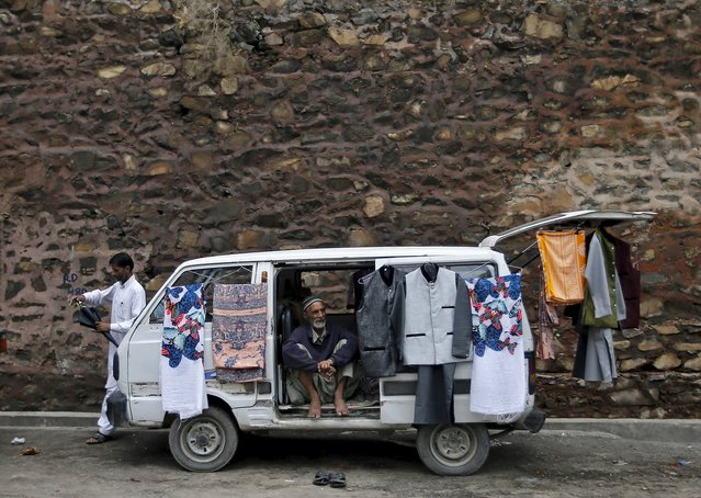 A Kashmiri cloth seller sits inside a van as he waits for customers along the roadside in Srinagar August 3, 2015. (Photo by Danish Ismail/Reuters)