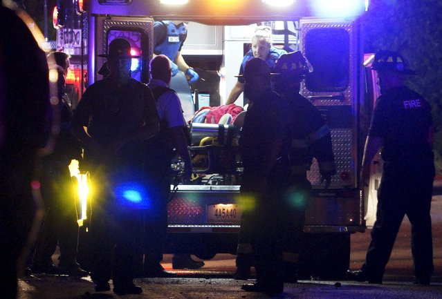 A black man is loaded into an ambulance after a police officer involved shooting in Ferguson, Missouri August 9, 2015. Two people were struck by gunfire in the midst of a late-night confrontation on Sunday between riot police and protesters, police said, after a day of peaceful events commemorating the fatal shooting of an unarmed black teenager by a white officer one year ago. (Photo by Rick Wilking/Reuters)