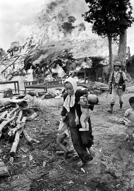 With a few salvaged belongings in the background, a Vietnamese woman carries a baby and pulls her daughter away as their home erupts in flames in July 1963. The woman and children may have been left behind so as not to slow other villagers escaping into the jungle
