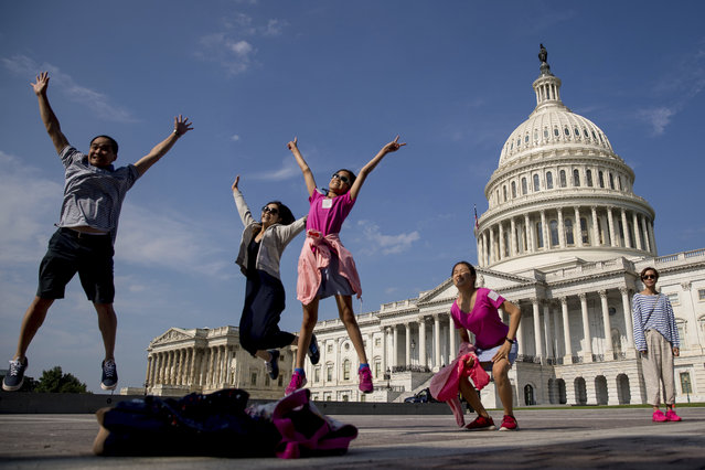 Tourists pose for a photograph in front of the Capitol Building in Washington, Monday, July 17, 2017. The Senate has been forced to put the republican's health care bill on hold for as much as two weeks until Sen. John McCain, R-Ariz., can return from surgery. (Photo by Andrew Harnik/AP Photo)