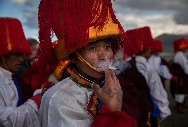 A Tibetan man smokes as he takes part in a local festival on July 27, 2015 on the Tibetan Plateau in Yushu County, Qinghai, China. (Photo by Kevin Frayer/Getty Images)