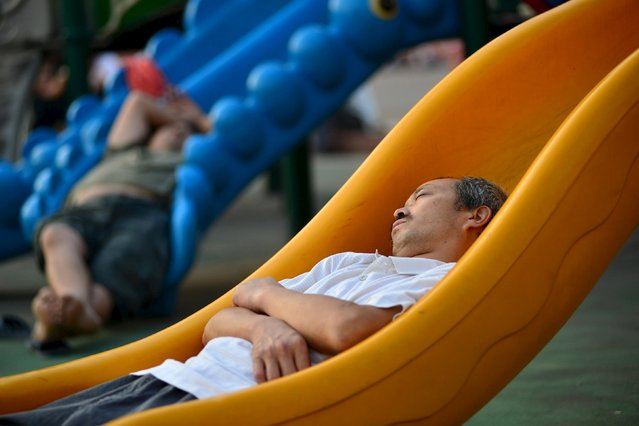 People sleep outdoors on slides after explosions hit Binhai new district, Tianjin, August 13, 2015. (Photo by Reuters/Stringer)