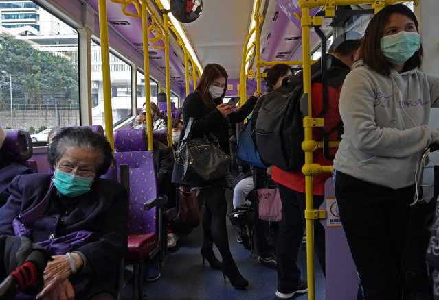 People wear protective face masks in a bus in Hong Kong, Tuesday, February 4, 2020. Hong Kong on Tuesday reported its first death from a new virus, a man who had traveled from the mainland city of Wuhan that has been the epicenter of the outbreak. (Photo by Vincent Yu/AP Photo)