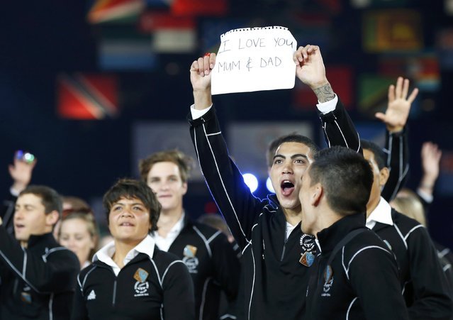 An athlete from New Zealand holds a note to his parents as the team enters the stadium during the opening ceremony for the 2014 Commonwealth Games at Celtic Park in Glasgow, Scotland, July 23, 2014. (Photo by Phil Noble/Reuters)