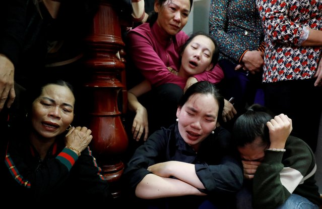 Relatives of John Hoang Van Tiep, a victim who was found dead in the back of a British truck last month, mourn near his coffin during his funeral at home in Nghe An province, Vietnam on November 27, 2019. (Photo by Reuters/Kham)